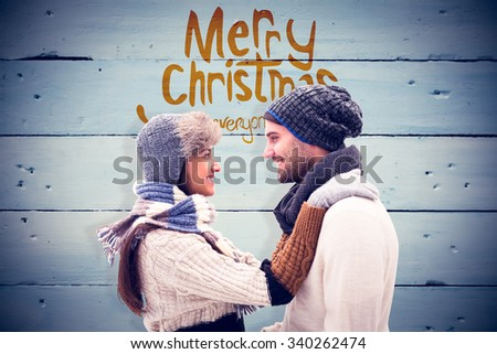 Young winter couple against painted blue wooden planks - stock photo