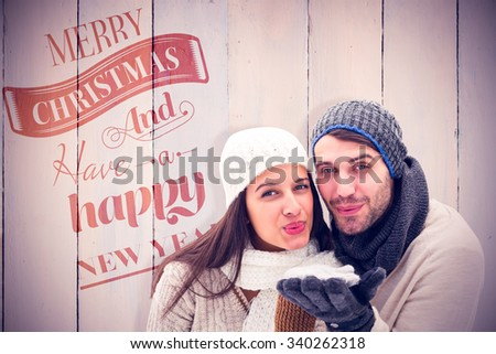 Young winter couple against wooden planks - stock photo