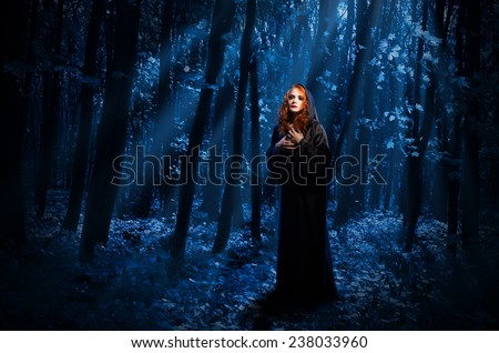 Young witch at night forest - stock photo