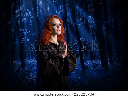Young witch at night in the moonlight forest - stock photo