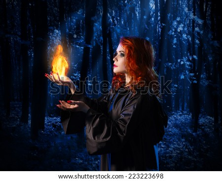 Young witch at night in the moonlight forest with flame - stock photo