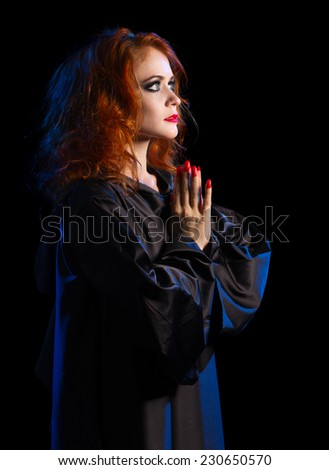 Young witch girl isolated on black - stock photo