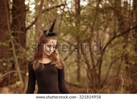 young witch in forest - stock photo