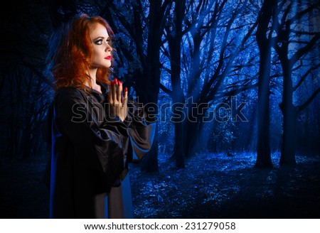 Young witch in the night forest - stock photo