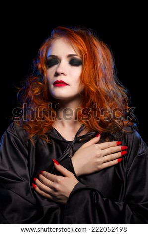 Young witch isolated on black - stock photo