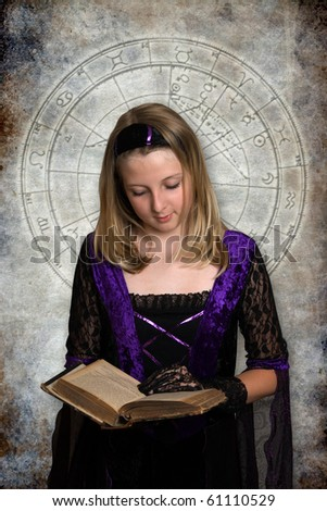 young witch with an old esoteric book - stock photo
