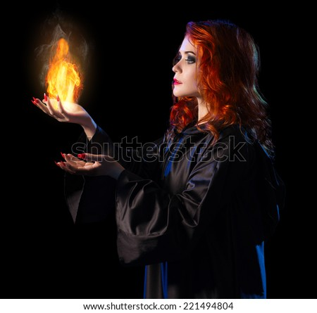 Young witch with flame isolated on black - stock photo