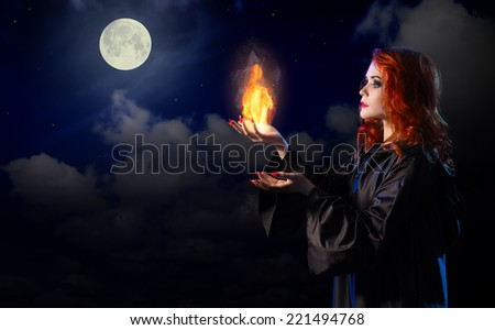 Young witch with flame on night sky background - stock photo