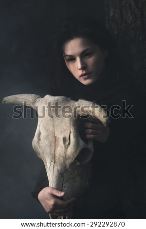 Young witch with skull in night forest - stock photo