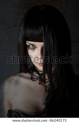 Young witch with yellow eyes and black long hair, textured background