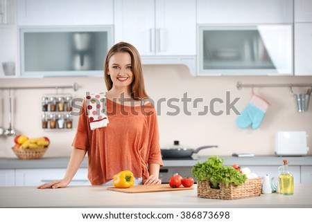 Young with with basket of fresh vegetables in the kitchen