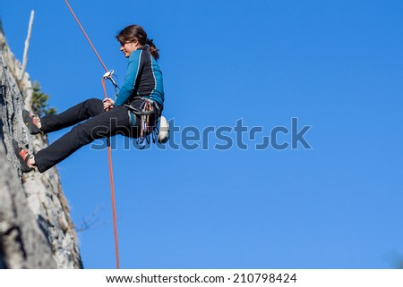 Young woman abseiling steep rock face - stock photo
