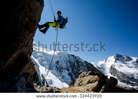 Young woman abseiling steep rock in the mountains - stock photo