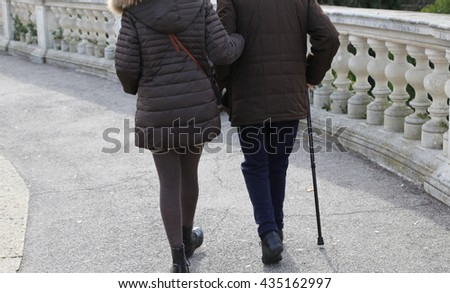young woman accompanies the older gentleman with stick