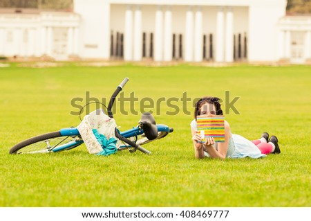 Young woman acting playful in city park during a sunny spring day with a book and blue bicycle near her