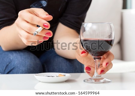 Young woman addicted to cigarettes and alcohol sitting by the table at home - stock photo