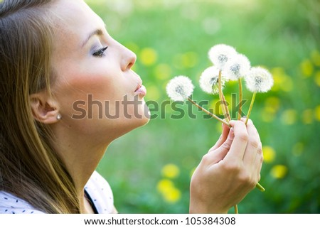 Young woman admiring dandelions