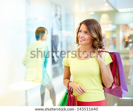 Young woman admiring shop-window - stock photo