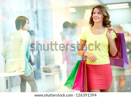 Young woman admiring shop-windows - stock photo