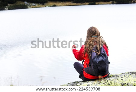 Young woman admiring the stillness of mountain  lake.Back view - stock photo
