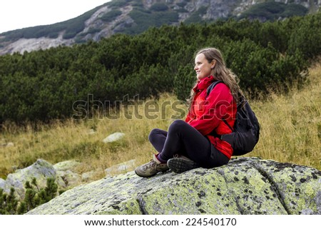 Young woman admiring the view during a hiking trip - stock photo