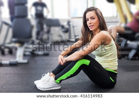 Young woman after exercising in a gym is looking at the camera