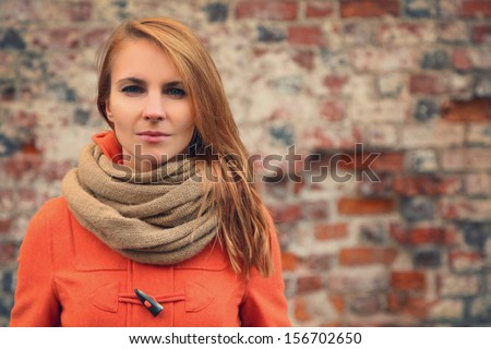 young woman against a brick wall - stock photo