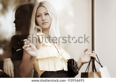 Young woman against a shop window - stock photo
