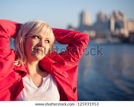 Young woman against river and urban background