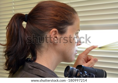 Young woman (age 25-30 ) looks and searches with binoculars and  looks out through Venetian blinds. Concept photo of curious, spy, nosy woman. - stock photo