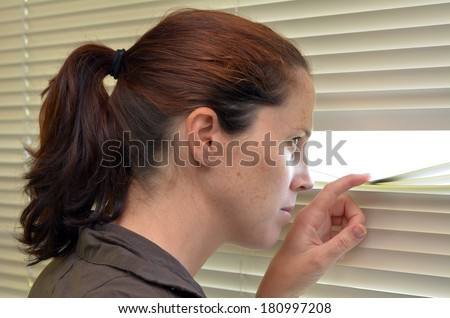 Young woman (age 25-30 ) looks out through Venetian blinds. Concept photo of curious, spy, nosy woman. - stock photo