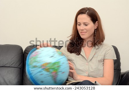 Young woman (age 30) search and examining the Globe  at home. Concept photo travel and education - stock photo