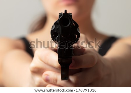 Young woman aiming a gun into you - stock photo