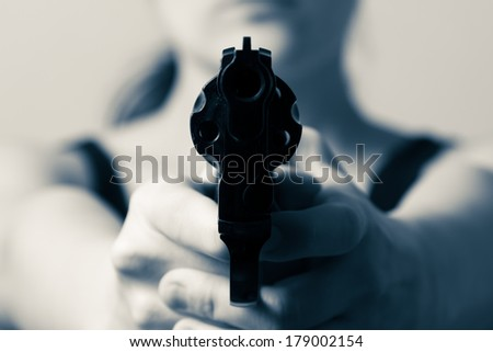 Young woman aiming a gun into you - processed colors - stock photo