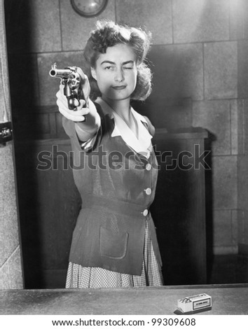 Young woman aiming with a handgun - stock photo