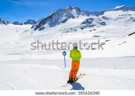 Young woman alpine skier on ski run in Pitztal winter resort, Austrian Alps - stock photo