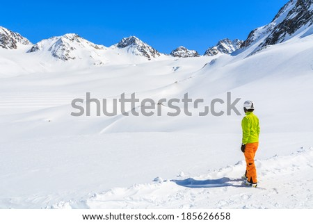 Young woman alpine skier stands in snow and looks at mountain peaks of Austrian Alps, Pitztal winter resort