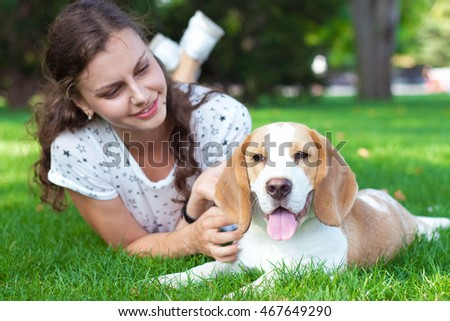 Young woman and a dog walking in the park. Happy girl and small cute dog playing on the grass in the park.