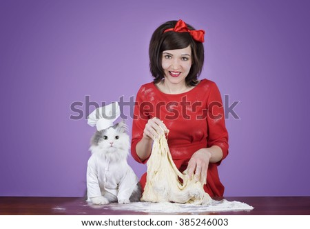 young woman and a fluffy cat preparing dough