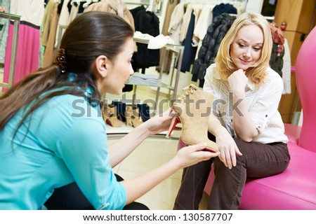 Young woman and assistant choosing footwear during shopping at shoe shop