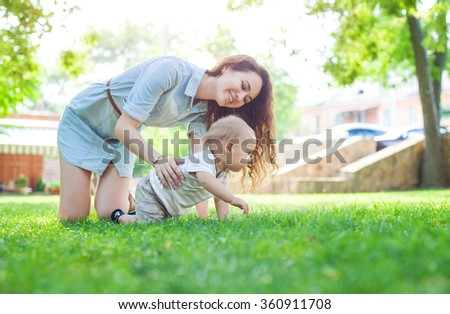 Young woman and baby son enjoying summer day in park - stock photo