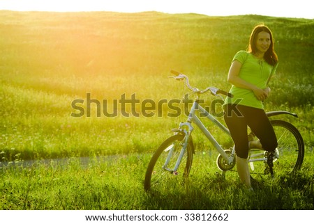 Young woman and blue bicycle at sunset. - stock photo