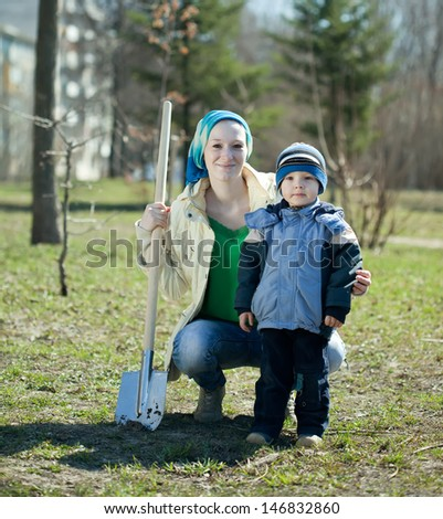 young woman and boy  with spade  in park - stock photo