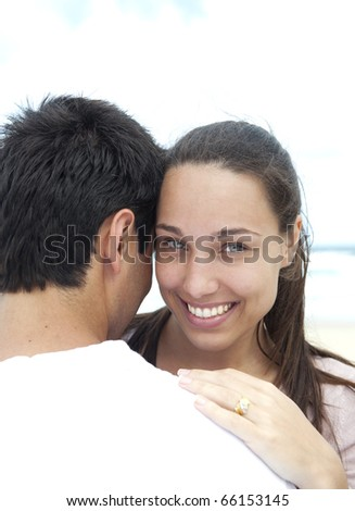 Young woman and boyfriend on the beach smiling