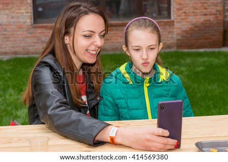 Young Woman and Brunette Girl Taking Selfie Self Portrait or Looking at Screen Together While Sitting Together at Outdoor Picnic Table - stock photo