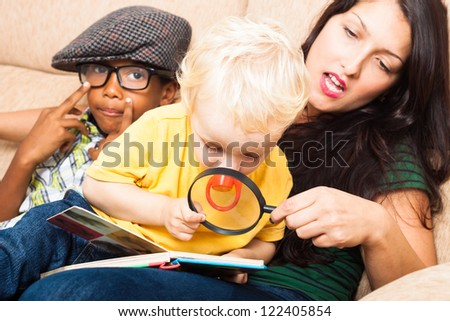 Young woman and children reading book with magnifying glass. - stock photo