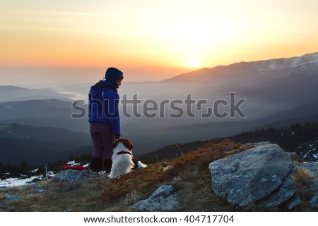Young woman and dog at sunrise high in the mountain, Rila Mountains, Bulgaria - stock photo