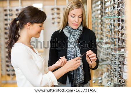Young woman and female customer holding glasses at store - stock photo