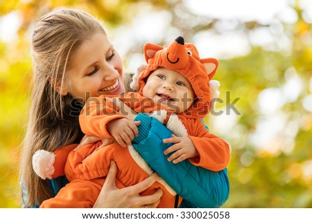 Young woman and her baby son in autumn park, boy dressed in fox costume - stock photo