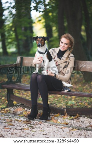 Young woman and her cute dog posing outdoor in autumn park - stock photo